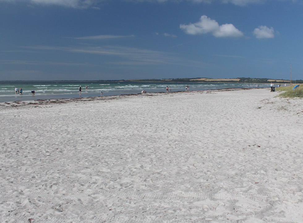 Bathers on the wide sandy beach with clear and inviting bathing water in Gudmindrup Lyng