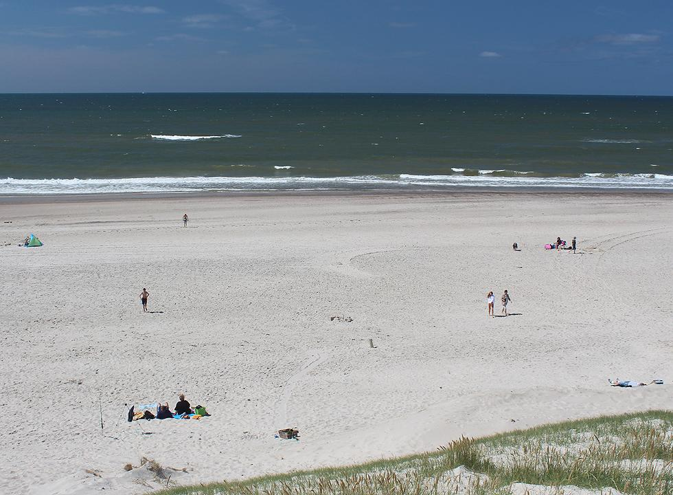 Bathers on the wide sandy beach in Haurvig
