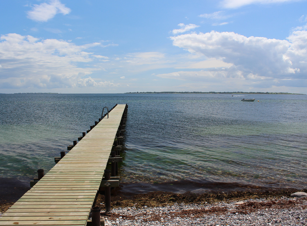 The long bathing jetty by the beach and the holiday homes in Horne Sommerland