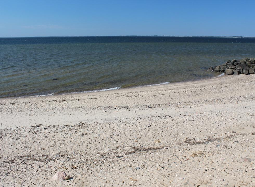 Clear bathing water by the beach of the holiday home area Hostrup