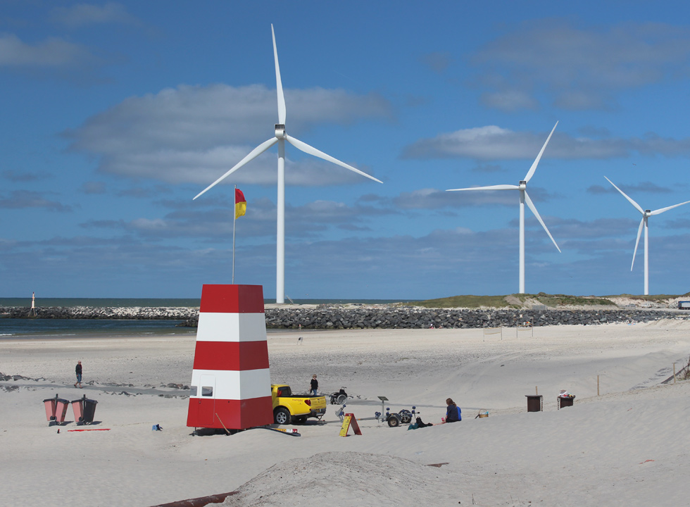 The large offshore wind turbines and the lifeguard tower by the beach in Hvide Sande