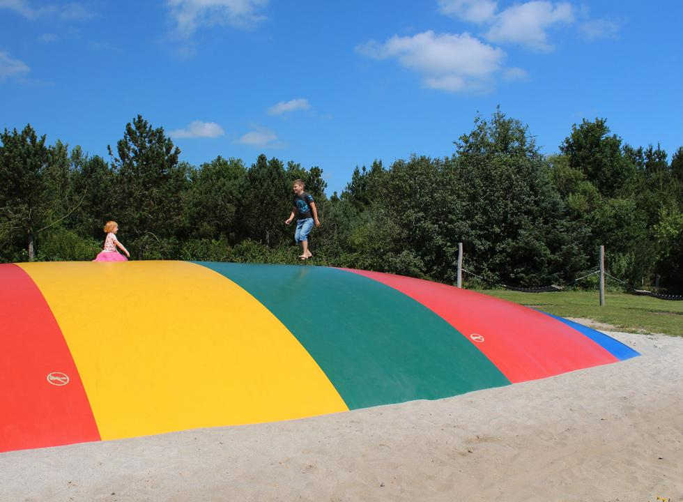 Children play on the large jumping pillow on the common area among the holiday homes in Jegum