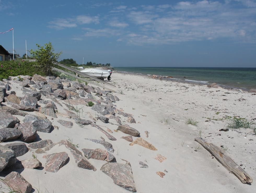 A slope with stones separates the holiday home sites from the beach in Jørgensø