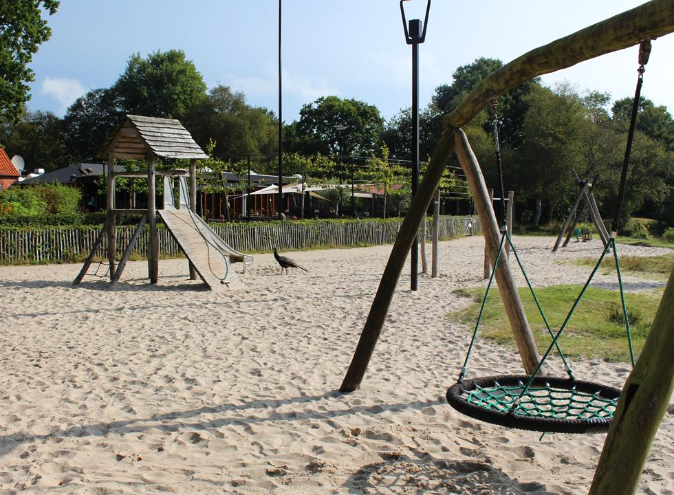 Fine playground with a peacock and play equipment by the lake shore in the holiday area Kvie Sø