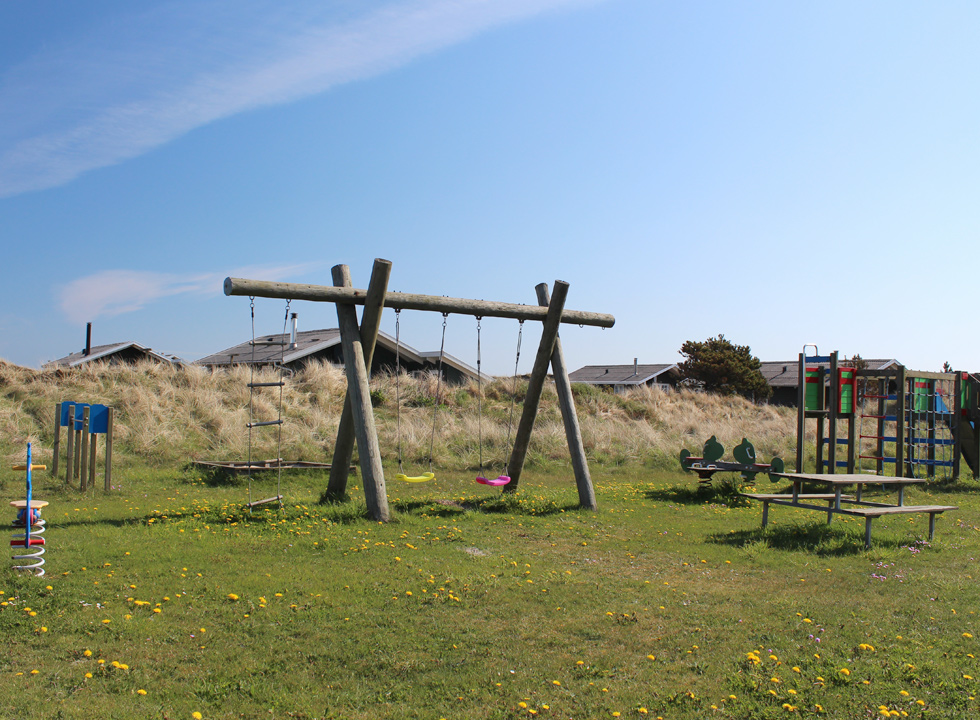 Playground on a green space by the holiday homes in Lild Strand