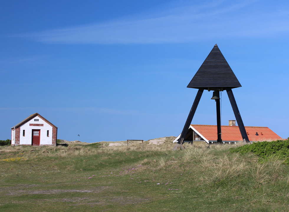 Well-maintained belfry behind the beach and the dunes of Lild Strand
