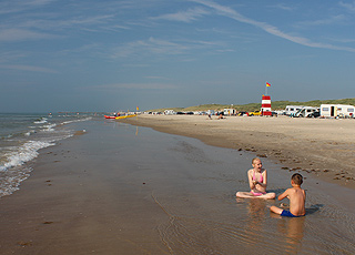 Children at the water's edge on the beach of Lokken