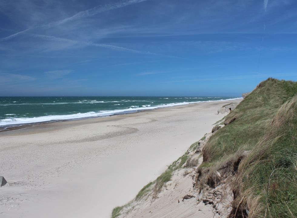 The wide sandy beach below the high dunes in Lyngby, Thy