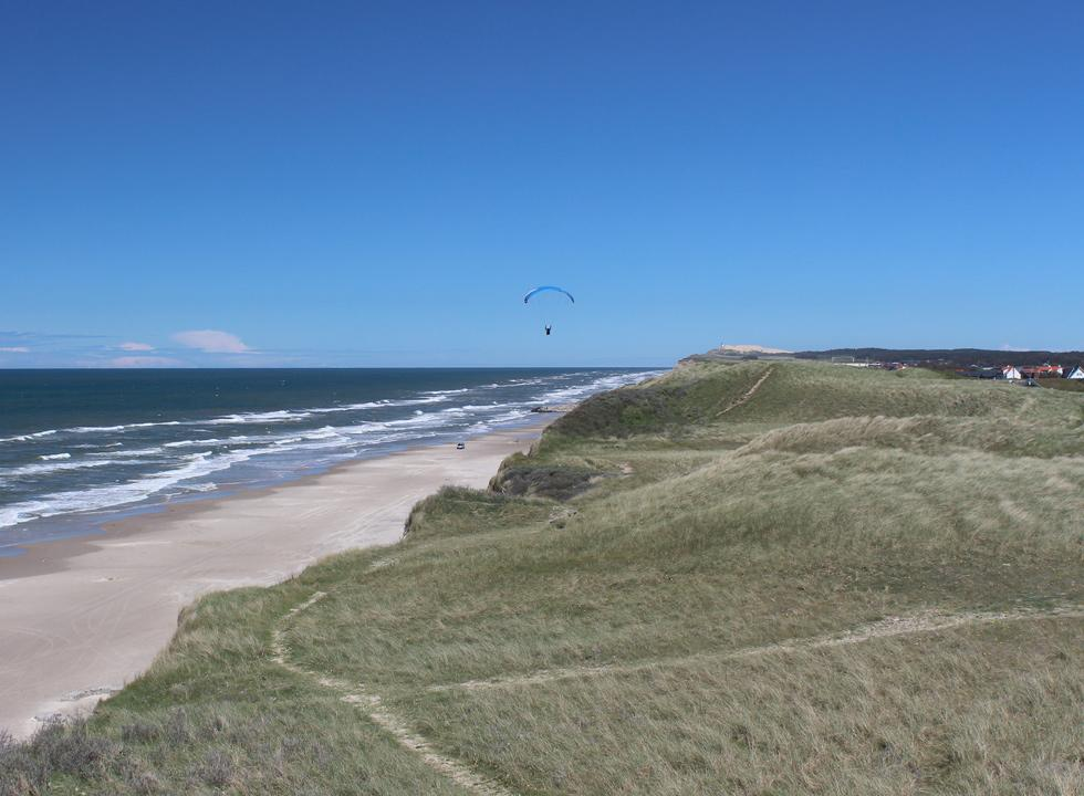 Paraglider in the air over the beach and the dune landscape with holiday homes in Nr. Lyngby