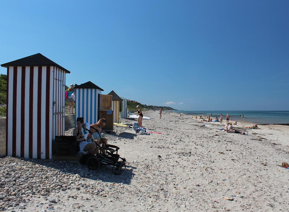 Bathers by the beach huts on the lovely bathing beach in the holiday area Rågeleje