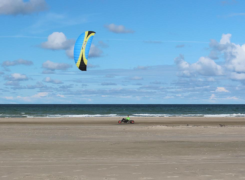 Kite buggy with wind in the sail on the wide sandy beach of the holiday home area Rødhus