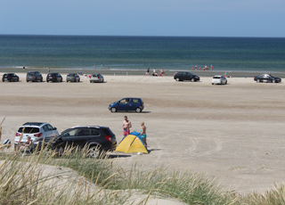 Bathing guests on the beach and in the water by the beach of Rødhus
