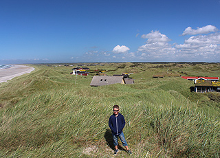 Holiday homes in the green and hilly landscape behind the beach in Rødhus