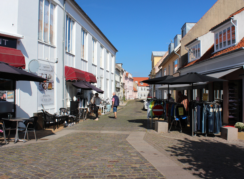 Cobbled pedestrian street with shops and eateries in Rudkøbing
