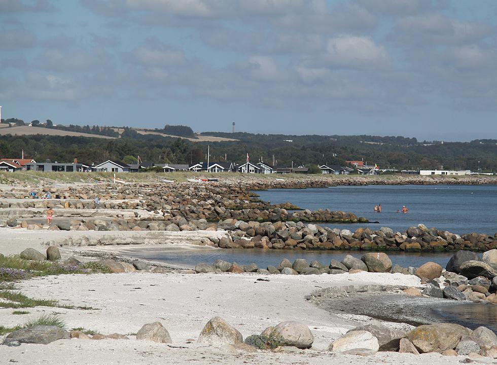 Bathers on the beach and in the water near the holiday homes in Sæby