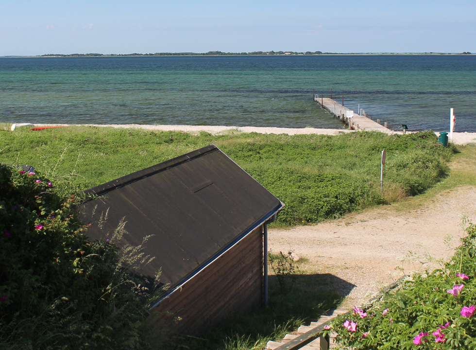 View of the beach and the bathing jetty from the stairs, which lead up to more holiday homes in Sandager Næs