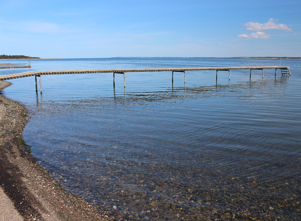 The long bathing jetty by the tranquil water of the Limfjord in Selde