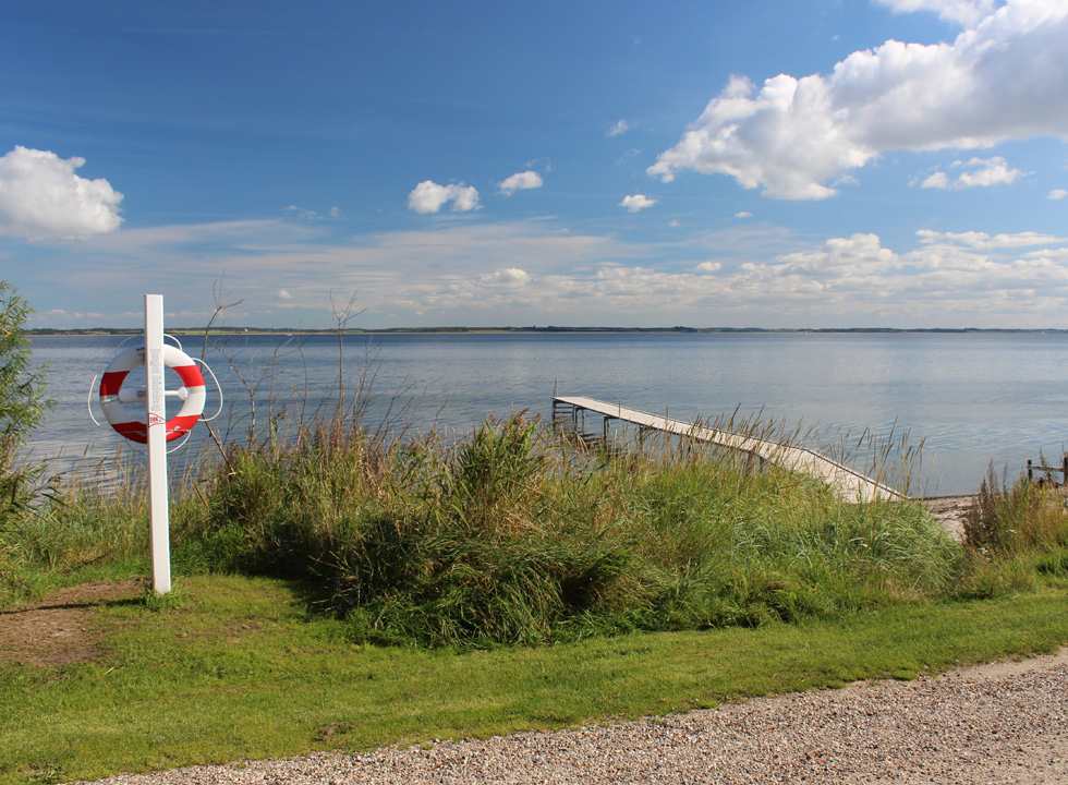 View of the beach and the bathing jetty from the gravel road behind the beach in Selde