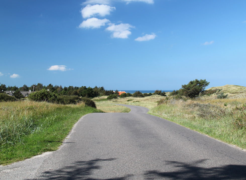 The road winds through the landscape with holiday homes towards the beach in Skiveren