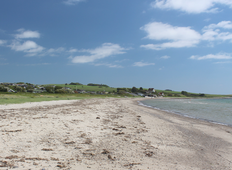 The wide sandy beach in Skødshoved is surrounded by green hills and holiday homes