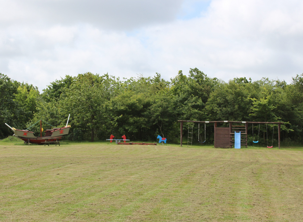 Playground and a large shared grass area by the holiday homes in Skyum