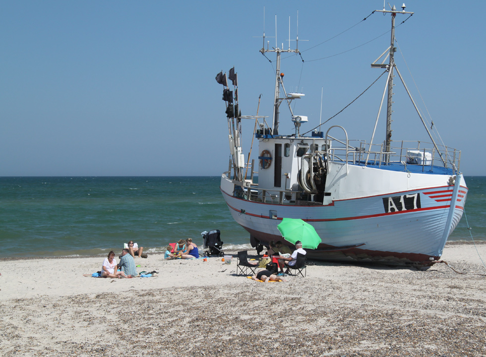Bathing guests relax, sheltered by a fishing vessel, on the beach of Slettestrand