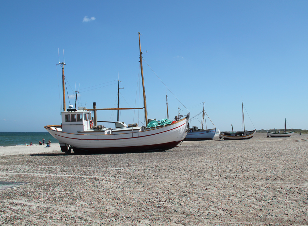 Local fishing vessels and bathing guests on the beach in Slettestrand