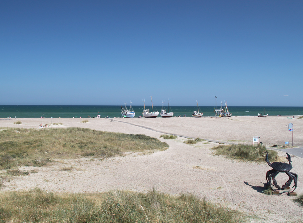 The wide sandy beach with a wooden path from the parking place to the water's edge in  Slettestrand