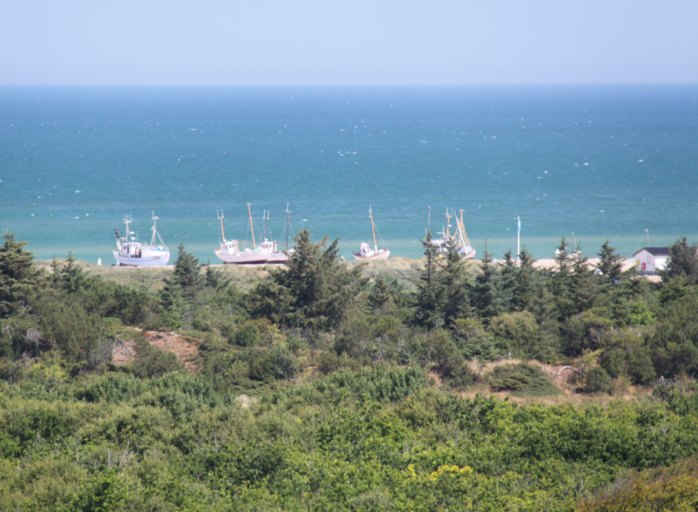 View of the fishing vessels on the beach in Slettestrand from the hills behind the shore