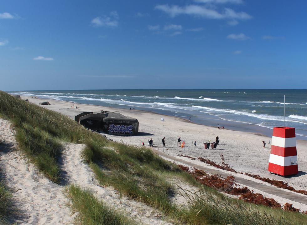 The lovely sandy beach with life guard tower, bunkers and high dunes in Sondervig
