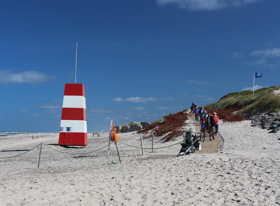 The beach in Sondervig with lifeguard towers, bunkers, blue flag and path between the dunes