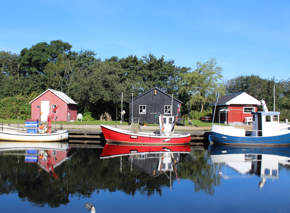 Idyllic harbour houses and fishing boats, which reflect in the water, in the harbour of Stauning