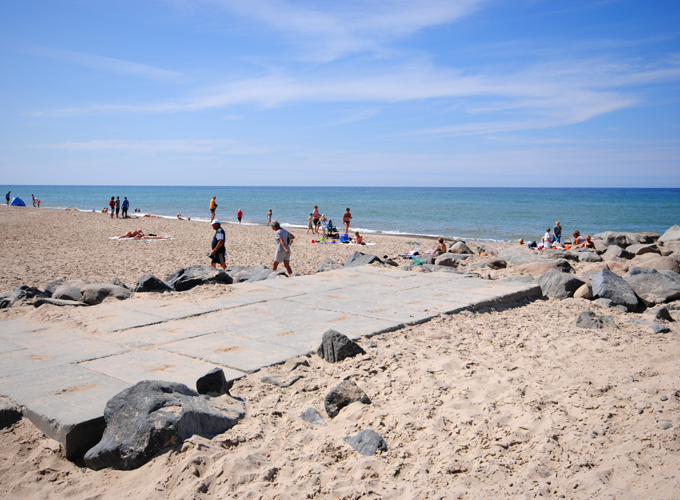 A summer day with bathing guests on the beach of Stenbjerg