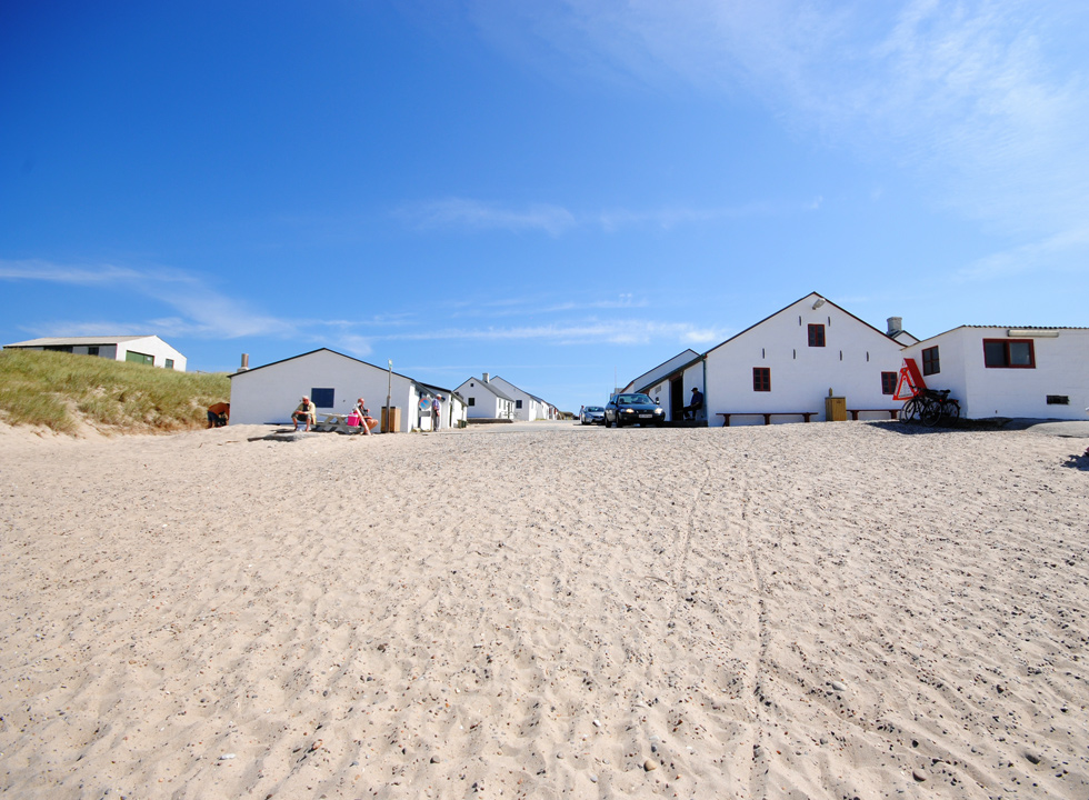 The wide sandy beach between the sea and the fishing houses in Stenbjerg