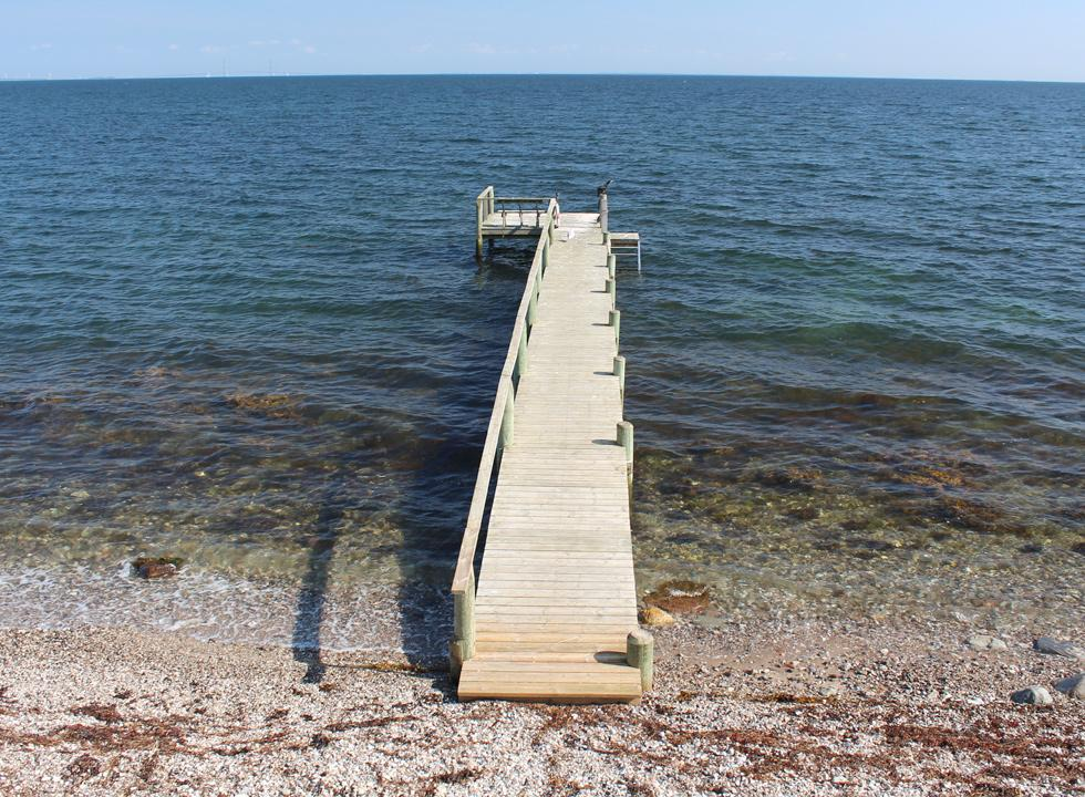Long bathing jetty by the stone beach in the holiday area Tårup