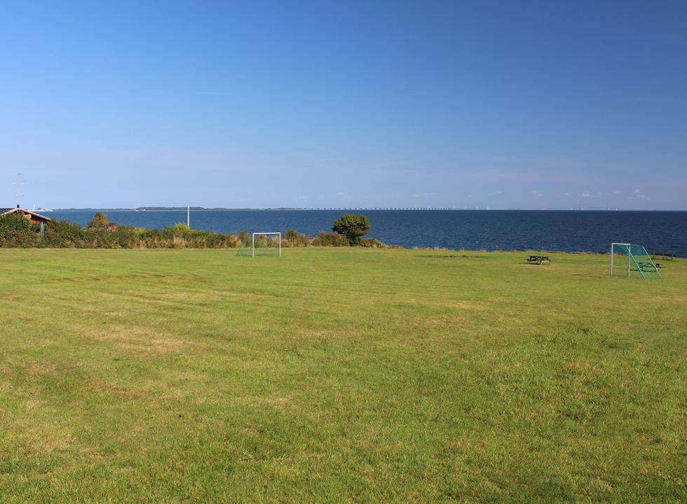 Green spaces with tables, benches and football goals behind the shore in the holiday home area Tårup
