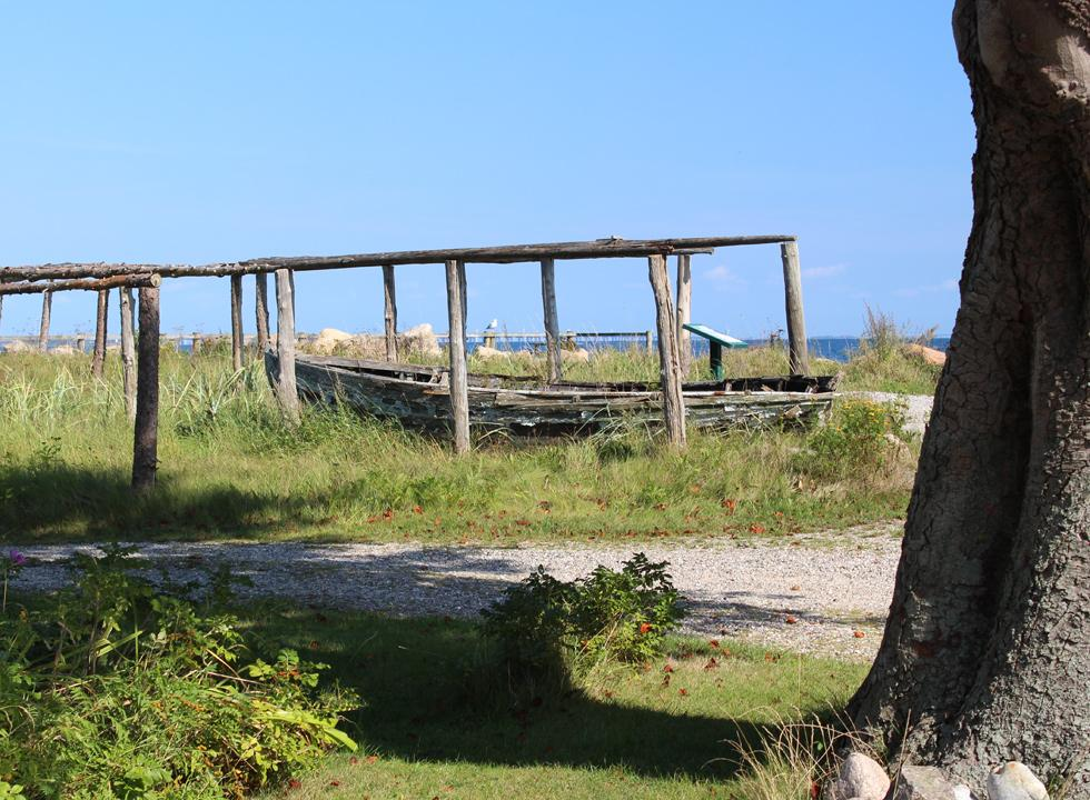 Historic wooden boat by the shore in the holiday area Tårup
