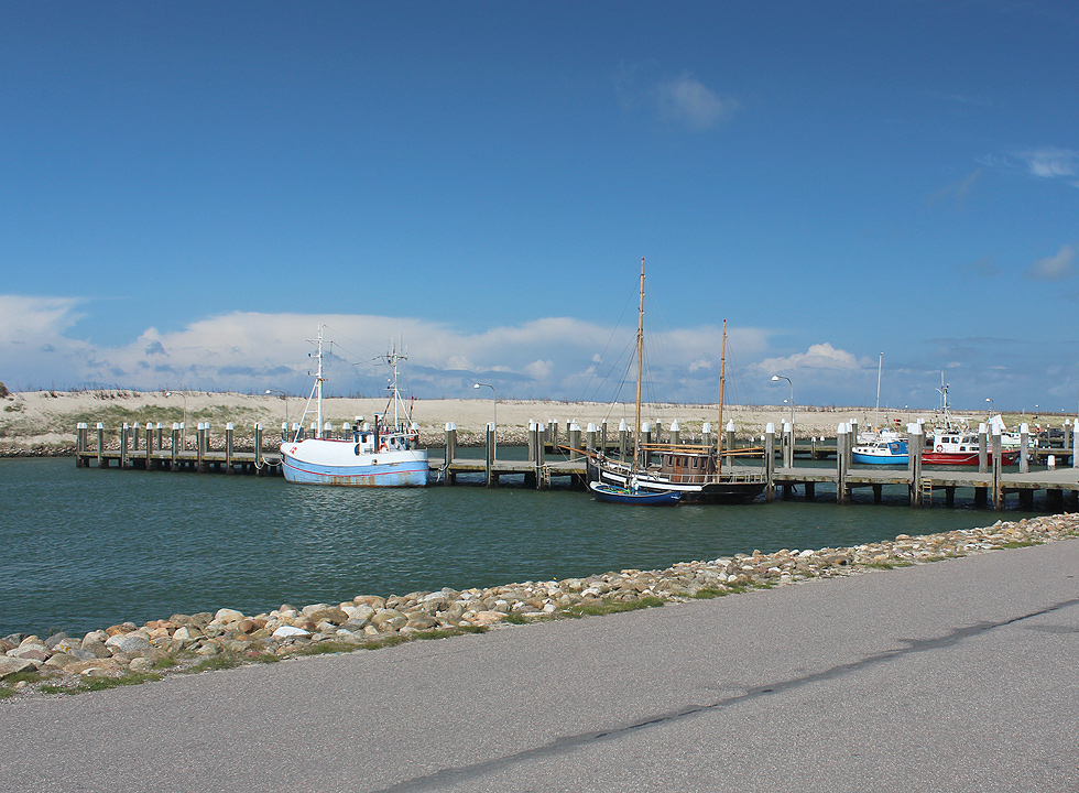 The cosy harbour with yachts and fishing boats right behind the dunes of the beach in Thorsminde
