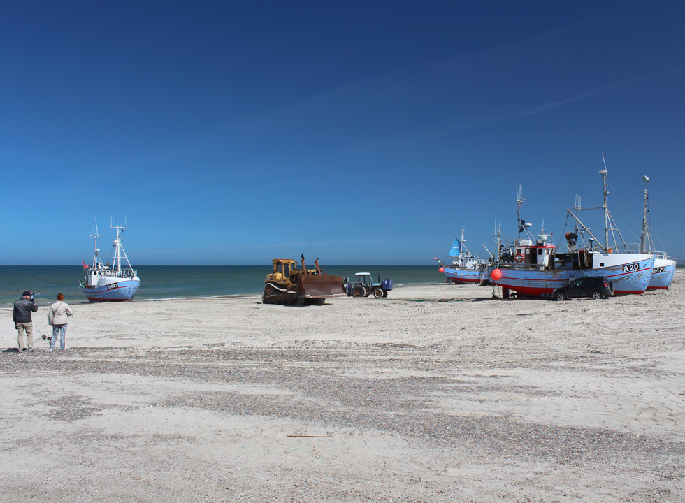 An excavator is pulling a fishing boat up on the beach in Thorup Strand