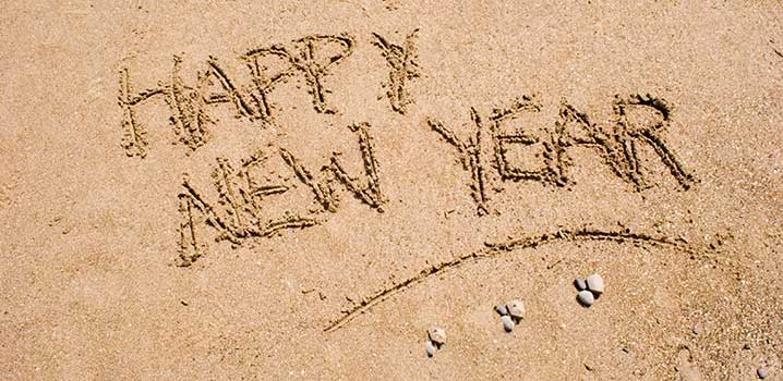 Happy New Year is written in the sand on the beach