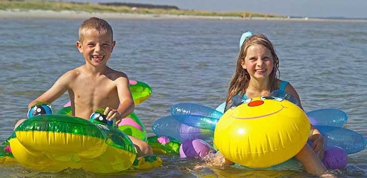 Two children on their separate inflatable animals in the water by the beach
