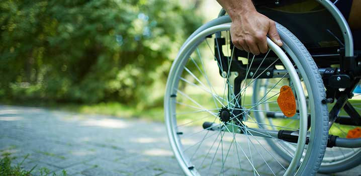 Man in a wheelchair on a flagstone path in a green area