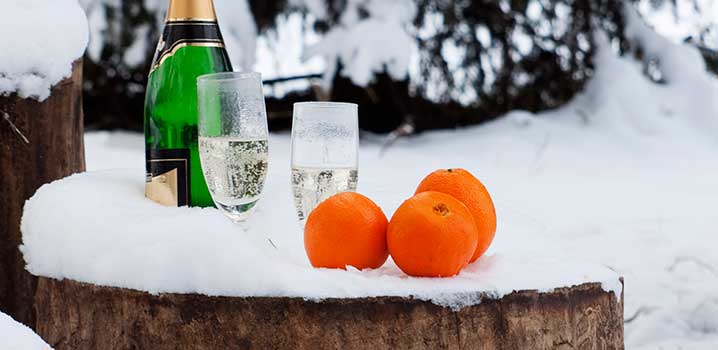 Champagne and oranges on a tree stump in the snow
